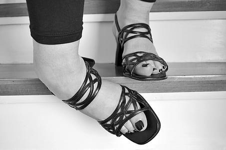 grayscale photo of person wearing heeled sandals