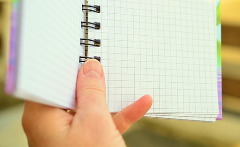 person holding spring notebook