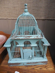 blue steel birdcage on brown table