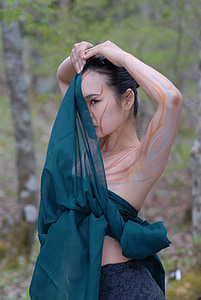 woman covering face with green textile