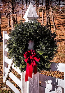 green and red wreath hang on white wooden fence during daytime