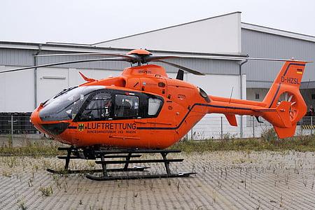 orange helicopter on ground near building