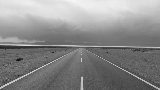 greyscale photo of road and sky with clouds