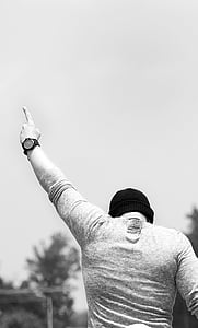 man wearing knit hat pointing his left hand at the sky during day