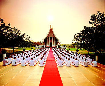 people sits on ground front of temple at sunset