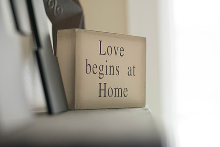 selective focus photography of love begins at home decorative wood block on white shelf