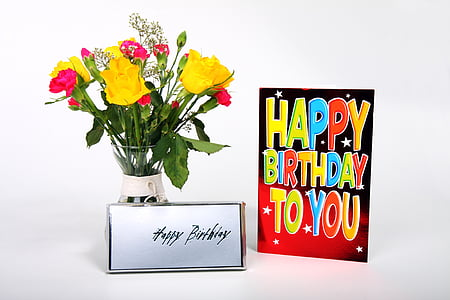 yellow, green, and red flower arrangement beside birthday greeting card