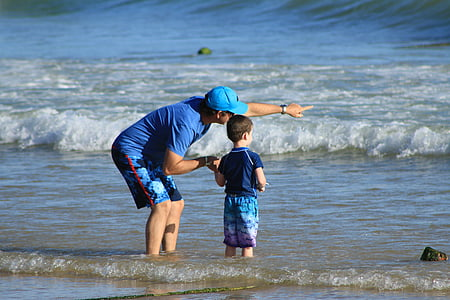 man and boy standing on shore
