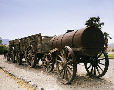 brown wooden carriage on roadway with barrel