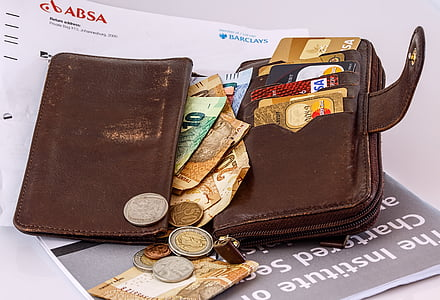 photo of brown leather wallet filled with mone y