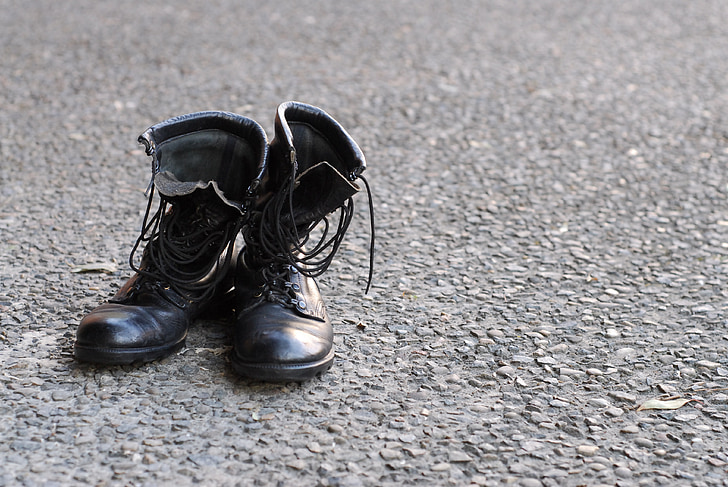 black leather combat boots on gray surface