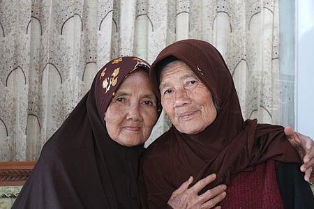 two woman sitting wearing hijabs