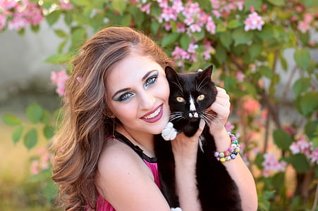 woman wearing pink top holding black cat