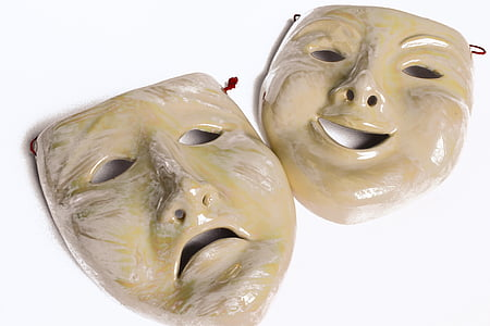 beige happy and sad masks on white surface