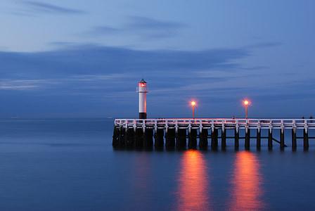 white lighthouse beside dock