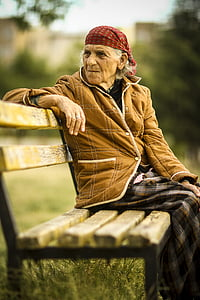 woman wearing brown jacket sitting on brown wooden bench