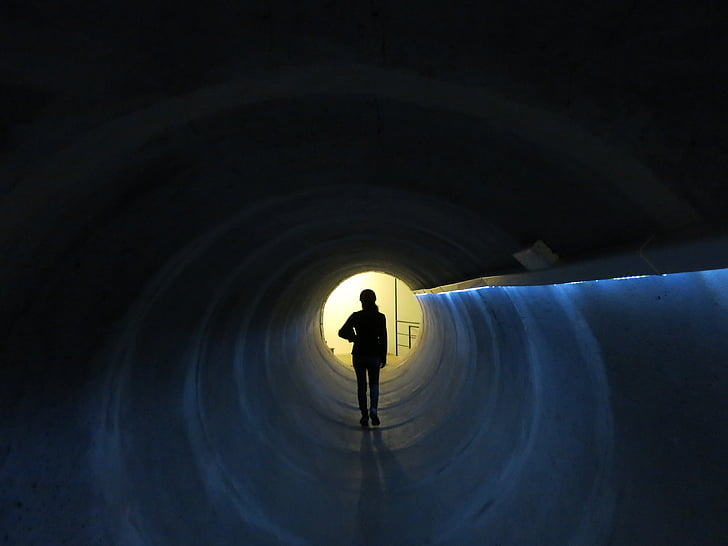 person standing inside tunnel