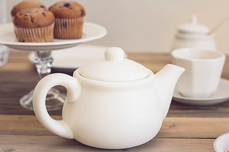 white ceramic teapot near footed cupcake stand