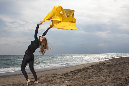 photo of woman in black wetsuit swaying yellow scarf
