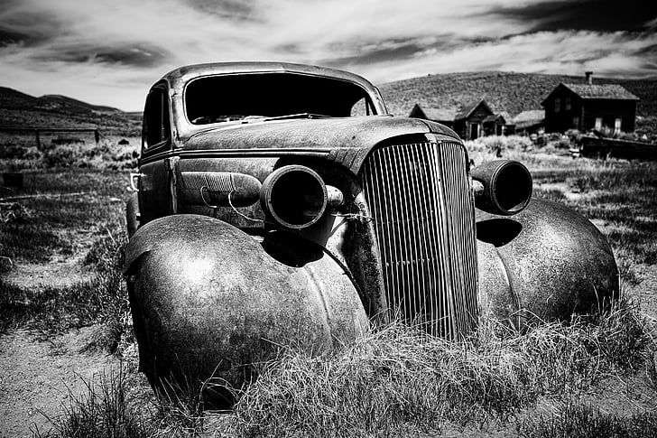 grayscale photo of abandoned car