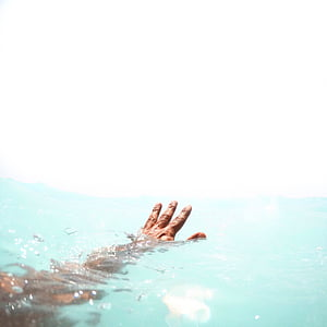 left human hand on body of water