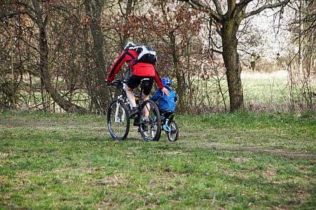 man riding bike while guiding boy riding bike taken at daytime