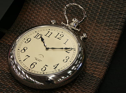 round silver-colored pocket watch time check at 10:10