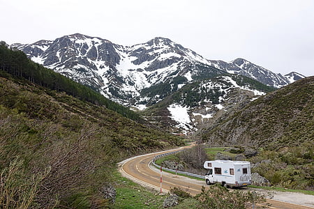 white class C motor home traveling on road