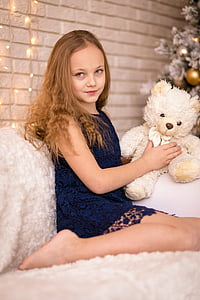 girl wearing blue floral sleeveless dress while holding white bear plush toy