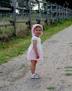 toddler in white and pink dress on brown pathway beside brown fence