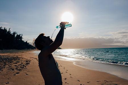 man holding bottle on seashore near body of water