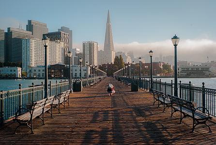 wooden bridge towards city skyline during daytime