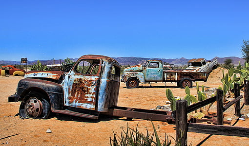 rusted vehicles on desert