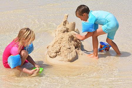 boy and girl build sand castle