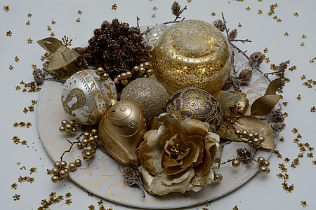 gold Christmas ornaments on white plate