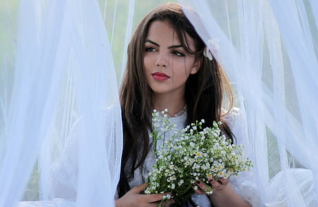 woman in white puff-sleeved top holding bouquet of baby's breath flowers