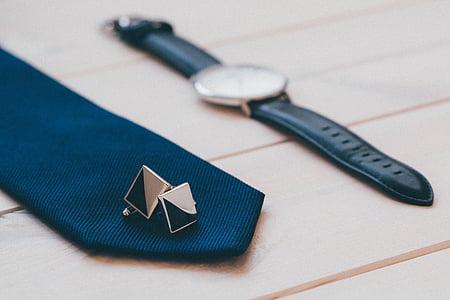 round silver-colored watch near black cufflinks and blue encktie