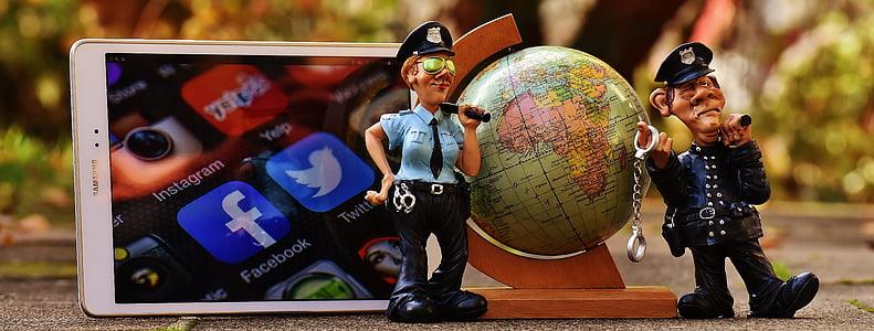 police man figurine beside smartphone