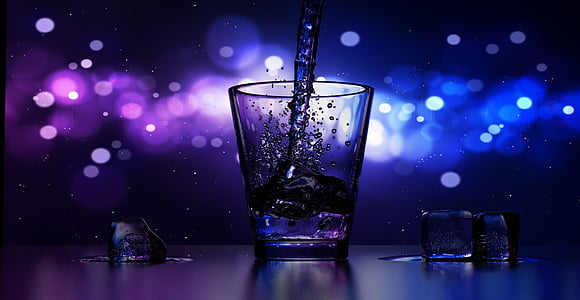 bokeh time lapse photography of liquid poured on shot glass