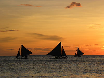 silhoutte of sailboats during sunset