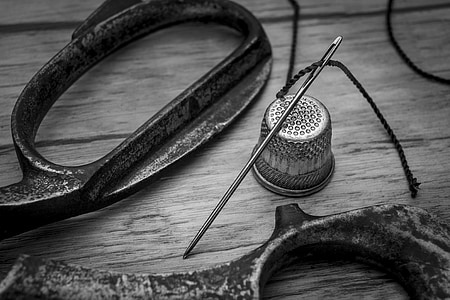 scissors, sewing needle, and thimble grayscale photo