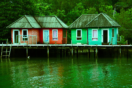 red and green house on body of water