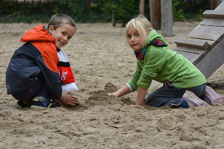 boy and girl playing on sand outdoors during daytime