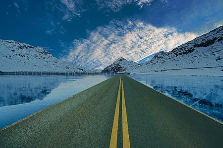 landscape photography of pavement road near body of water and snow covered mountain