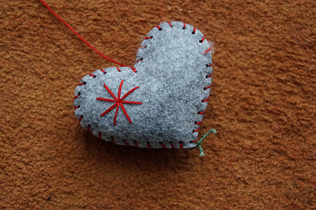 gray heart-themed pincushion on brown textile