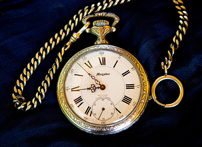 gold-colored roman pocket watch