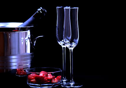 two empty clear wine glasses beside clear glass bowl with strawberry fruits