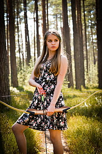 woman wearing tank mini dress holding composite bow and arrow in forest