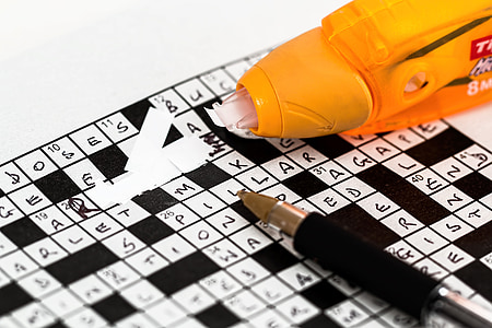 black and white crossword puzzle with pen and correction tape