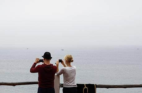 man and woman taking photo at the sea